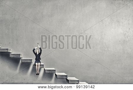 Young businesswoman on staircase proclaiming something in horn