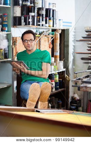 Portrait of relaxed worker using digital tablet while sitting in paper factory
