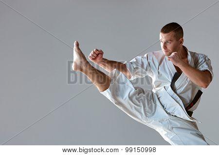 Man in white kimono training karate
