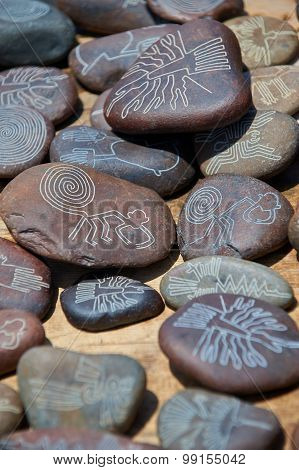 Pebbles souvenirs with Nasca line drawings, like monkey, condor, colibri poster