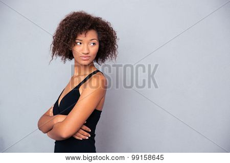 Portrait of a serious african woman with arms folded standing over gray background and looking away