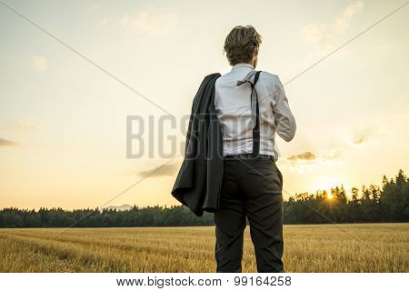 Young Successful Businessman Standing In Wheat Field Looking Gazing Into The Future