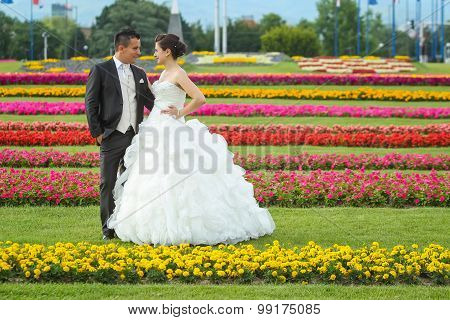 Bride And Groom Standing On Lawn With Flowers