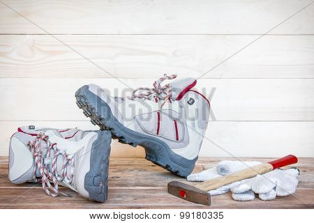 Pair Of Work Boots With Gloves And Hammer On Wooden Background.