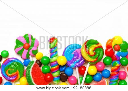 Bottom border of colorful candies over white