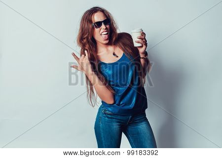 crazy woman in sunglasses showing tongue rock on gesture signs of positive emotions  and holding a c