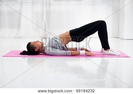 Bridge pose sporty woman doing warming up exercise for spine, backbend, arching stretching her back