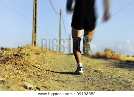 Back View Of Young Sport Man Legs And Feet Running On Countryside Track With Power Line Poles