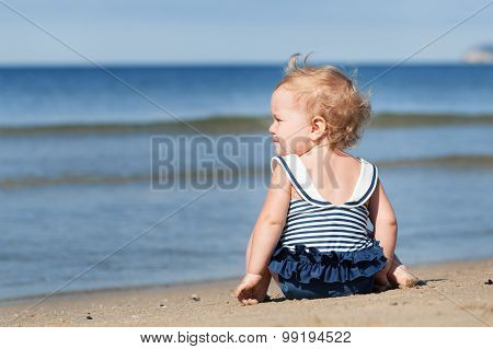 Little Girl Sitting On Beach In Swimsuit And Dreams