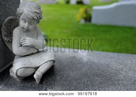 Antique marble statue of a Cherub angel with arms folded peacefully