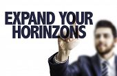 Business man pointing the text: Expand Your Horizons poster