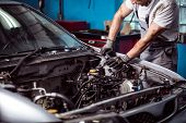 Picture of uniformed auto mechanic maintaining car engine poster