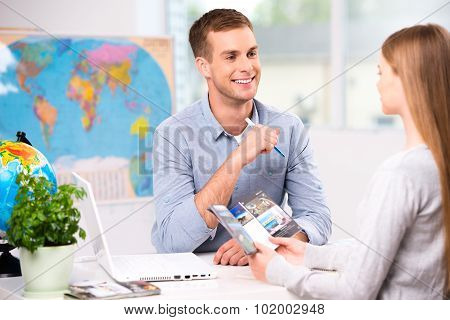Photo of male travel agent and young woman. Young man smiling and offering vacation options for female tourist. Travel agency office interior with big world map poster