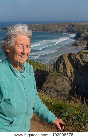 Elderly female pensioner in her eighties with walking stick by beautiful coast scene Cornwall