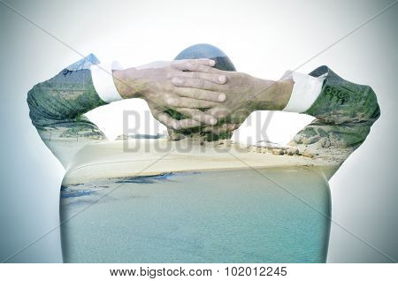 double exposure of a young businessman seen from behind relaxing in his office chair and a relaxing beach