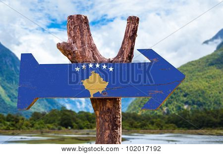 Kosovo Flag wooden sign with mountains on background poster