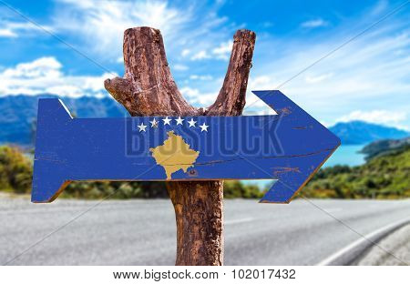 Kosovo Flag wooden sign with road background poster