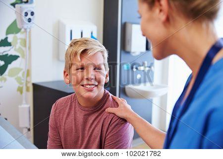 Teenage Boy Being Reassured By Doctor In Hospital Room