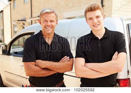 Portrait of a young and a middle aged tradesman by their van