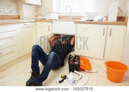 A plumber lying on his back to fix a kitchen sink