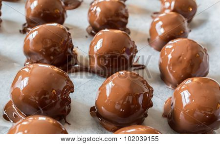 A Christmas favorite, homemade peanut butter chocolate balls. A mixture of peanut butter, nuts, sugar and other sweet stuff and then dipped in milk chocolate.