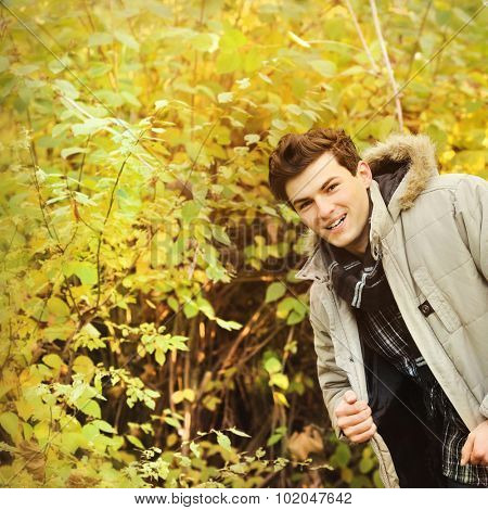 Smiling guy portrait wearing hoodie jacket and plaid shirt against autumn trees.
