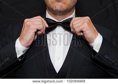 Gentleman In Black Tie Straightens His Bowtie