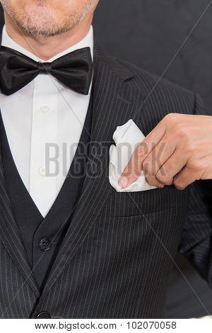 Gentleman In Black Tie Fixes Pocket Square, Vertical