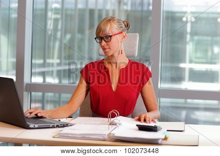 caucasian business woman in eyeglasses working on laptop in her office