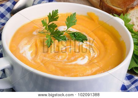 Pumpkin puree soup with cream and parsley on soup plate close-up poster
