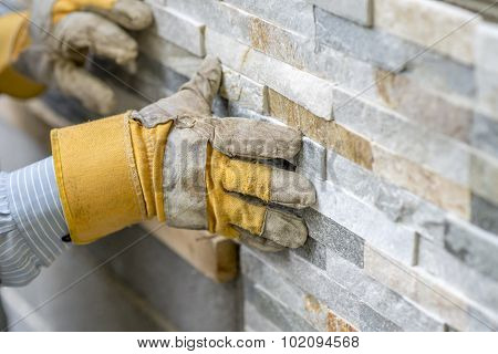 Closeup Of Manual Worker In Protection Gloves Pushing The Tile Into The Cement On The Wall