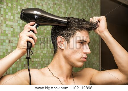 Shirtless young man drying hair with hairdryer