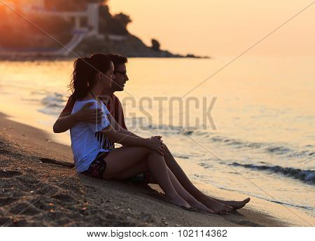 Young Lovers Sitting In The Sand On Shore