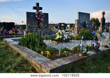 Grave, tombstone in the cemetery. All saints day. All hallows. 1st november. flowers and candles on tomb stone in churchyard. slovakia, europe poster