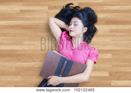 Student Holding Book And Sleeping On The Floor