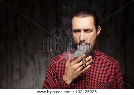 Attractive young bearded man is relaxing with cigarette