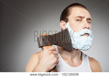Cheerful man is shaving his beard with axe. He has foam over his face. The man is looking at the camera seriously. Isolated poster