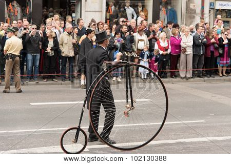 MUNICH, GERMANY - 19 October 2015: Tent owners and breweries parade at the beginning of Oktoberfest - Riding a penny farthing