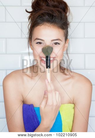 Applying make up concept, young attractive smiling woman covered with towel with cosmetic brush
