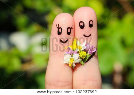 Finger art of a Happy couple. Man is giving flowers to a woman.