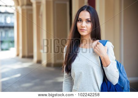 Portrait of attractive female student standing outdoors and lookign at camera