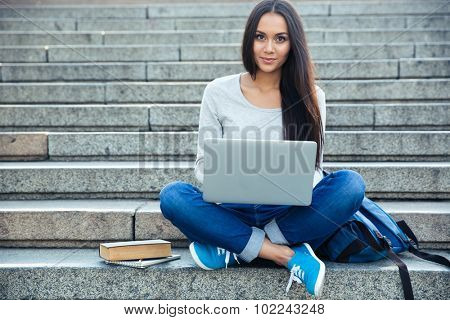 Portrait of a happy young woman sitting on the city stairs and using laptop computer outdoors
