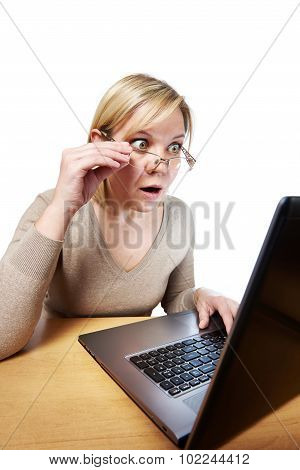 Frightened woman with glasses looking at a laptop isolated poster