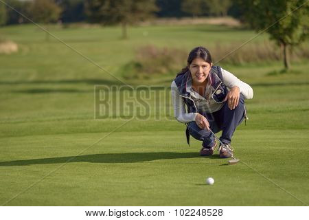 Female Golfer Lining Up A Putt