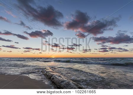 Log Washed Up On The Shore Of Lake Huron At Sunset