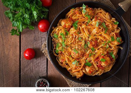Pasta linguine with meatballs in tomato sauce.