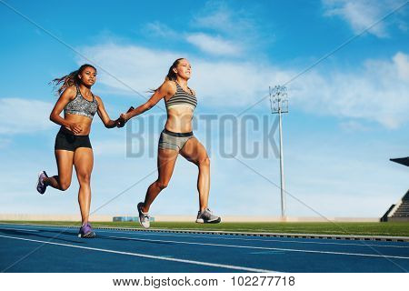 Female Relay Racing Team On Racetrack