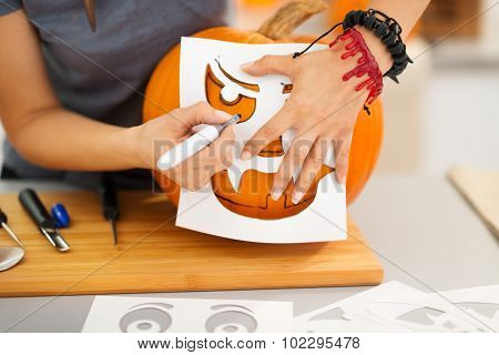 Woman Using Stencils To Carve Pumpkin Jack-o-lantern. Closeup