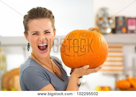 Young Woman Scaring With Big Halloween Pumpkin Jack-o-lantern
