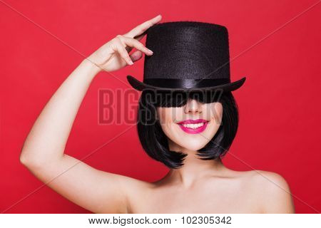 fashion model in hat cylinder, on red background